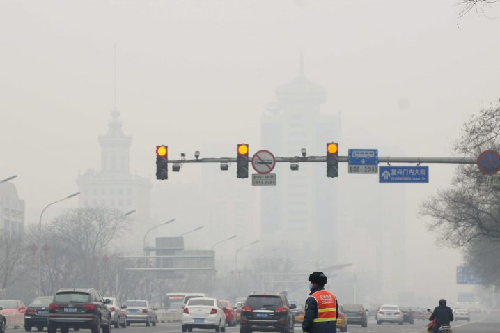 epa04098577 A picture made available 24 February 2014 shows a traffic worker looking at the traffic as smog covers Beijing, China, 23 February 2014. Due to smog alerts, a city in northern China has banned a fifth of residents' vehicles from roads, reports stated since 23 February. In Beijing, an orange alert had been issued on 21 February due to smog which is the second-highest of four levels of urgency. The Environmental Protection Ministry has sent 12 inspection teams to Beijing, Tianjin, Hebei and surrounding areas to check on compliance to measures to reduce air pollution. EPA/JASON FAN CHINA OUT